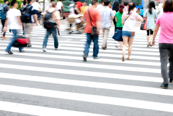 Pedestrians crossing a busy city traffic road at a zebra pedestrian crossing